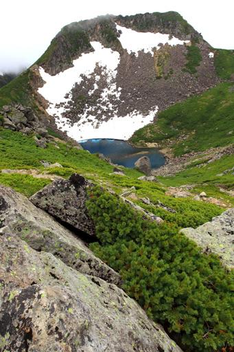 残雪の山肌と池の風景