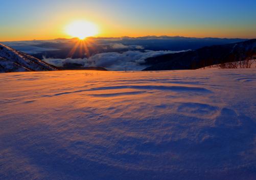 南アルプスを抱くご来光とバラ色に染まる雪原