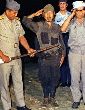 1974年3月、軍刀を渡し敬礼をする元陸軍少尉の小野田寛郎さん(中央)=フィリピン・ルバング島(共同)