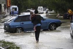 2012-07-23_Russia_ロシア南部クルイムスクで、冠水した道路を歩く母子=7日(ロイター)01