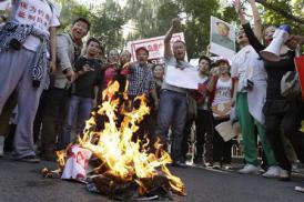 2012-09-24_China_【経済裏読み】中国版「アラブの春」は可能性ゼロ? SNSをぶった切る異常さ01_中国・北京の日本大使館近くで日本国旗を燃やして気勢を上げるデモ参加者=9月18日(AP)