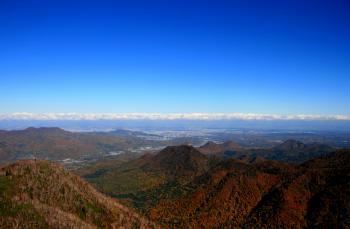 山肌の紅葉と、遠く札幌の街並み。