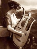 A postcard showing a girl playing a lyre-guitar_from Wikipedia